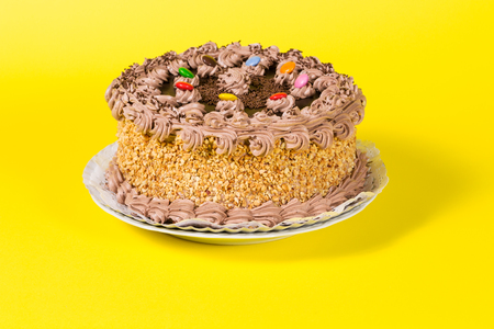 pastel de cumplea�os: Chocolate sabrosa y pastel de cumplea�os de avellana caramelos de colores adornado sobre fondo amarillo