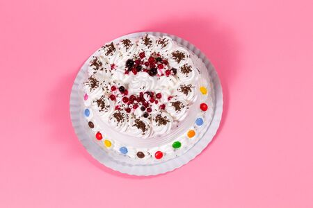 adorned: Tasty creamy birthday cake colorful candy adorned on pink background