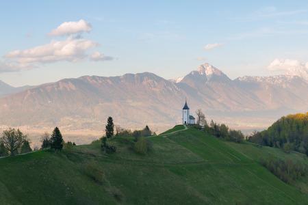 karavanke: Jamnik church on a hillside at sunset in Slovenia, Europe Stock Photo