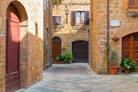 Beautiful narrow alley with traditional historic houses at Pienza city in Tuscany