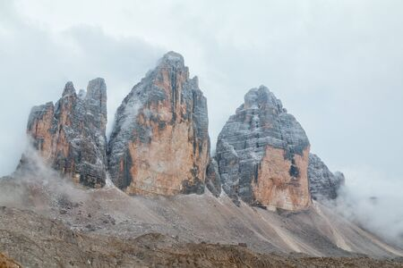 Tre Cime di Lavaredo in beautiful surroundings in the Dolomites at foggy weather in Italy, Europe (Drei Zinnen) Stock Photo