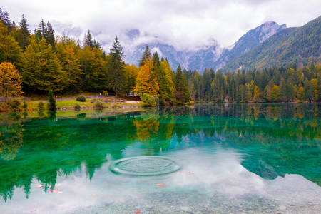 Beautiful lake, Fusine mountain lake in autumn and Mangart mountain in the background  in northern Italy alps, Europe Imagens