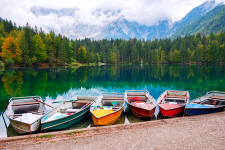 Lago di Fusine the mountain lake at boat and Mangart mountain in the background in north Italy alps, Europe Imagens