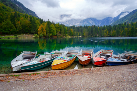Lago di Fusine the mountain lake at boat and Mangart mountain in the background in north Italy in Alps, Europe