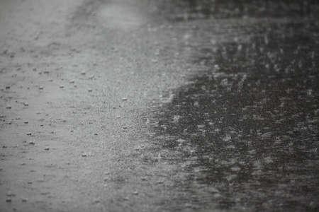gotas de agua: Lloviendo sobre asfalto Foto de archivo