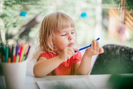 Cute little blonde adorable girl coloring with pencils at home. Girl trying to close felt pen. Early education concept