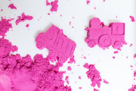 Truck and train made with a pink kinetic sand on a white background