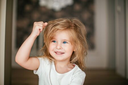 Little shaggy blonde baby girl with a hand up is smiling after her morning awaking