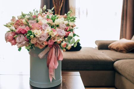 Modern bouquet of flowers in blue round box on a wooden table. Beautiful floral arrangement in a hat box. Flowers bouquet in headbox