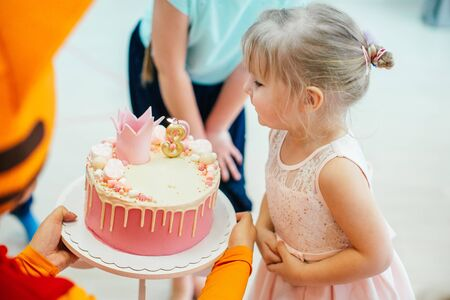 Three years old blonde adorable girl in a pink dress blowing candles on birthday pink cake with number three. Imagens