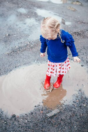 cute little blonde girl wearing red rain boots jumping into a puddle 写真素材