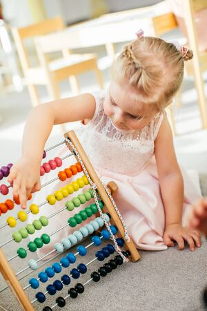 Cute little girl playing with wooden abacus at home. Smart child learning to count. Preschooler having fun with educational toy at home or kindergarten 写真素材