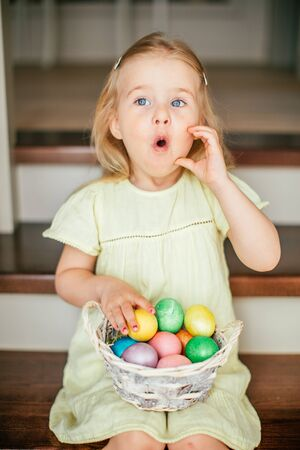 Cute little child girl with blonde hair on Easter day. Girl holding basket with painted eggs and sitting on the stairs at home.
