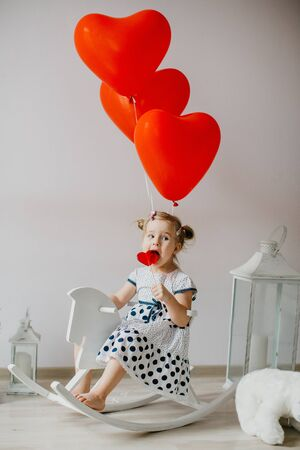 Adorable blonde girl eating a caramel Lollypop in the shape of a heart. Kid sitting on a white wooden horse with red heart shaped baloons.Valentines Day concept. 版權商用圖片