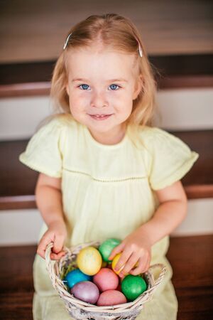 Cute little child girl with blonde hair on Easter day. Girl holding basket with painted eggs and sitting on the stairs at home
