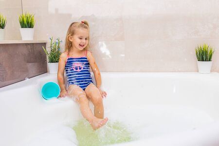 Little smiling blonde girl in blue swimsuit splashing in a big modern bathroom with foam. .Kids hygiene. Shampoo, hair treatment and soap for children.