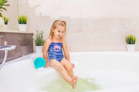 Piccola ragazza bionda sorridente in costume da bagno blu che spruzza in un grande bagno moderno con schiuma. .Igiene dei bambini. Shampoo, trattamento per capelli e sapone per bambini. Archivio Fotografico