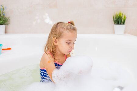 Little blonde smiling girl taking bubble bath in beautiful bathroom.Kids hygiene. Shampoo, hair treatment and soap for children. Kid bathing 스톡 콘텐츠