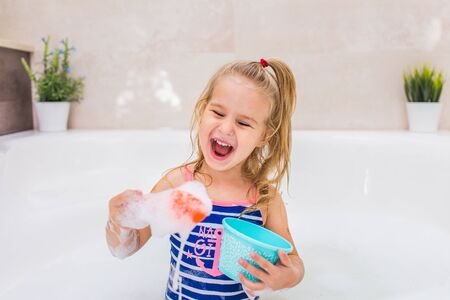 Funny little blonde girl taking bubble bath in beautiful bathroom.Kids hygiene. Shampoo, hair treatment and soap for children. Copyspace. 스톡 콘텐츠