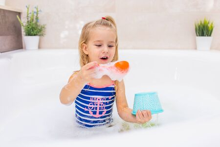 Little blonde girl taking bubble bath in beautiful bathroom.Kids hygiene. Shampoo, hair treatment and soap for children. Kid bathing in large tub.