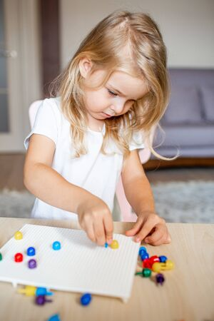 Little blonde girl in a white tshirt playing with plastic multicolor mosaic at home or preschool. Early education concept 写真素材 - 132180844