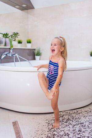 Felice bambina in un costume da bagno blu whetu che sta vicino alla vasca da bagno in bagno e urla con un sorriso Archivio Fotografico