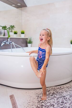 Happy little baby girl in a whetu blue swimsuit staying near bath tub in the bathroom and screaming with smile