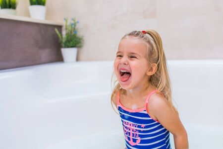 Little blonde girl in a large tub smiling and showing her tongue. Kids hygiene. Shampoo, hair treatment and soap for children. Copyspace 免版税图像