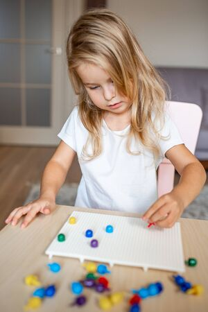 Little blonde girl in a white tshirt playing with plastic multicolor mosaic at home or preschool. Early education concept 写真素材 - 132180859