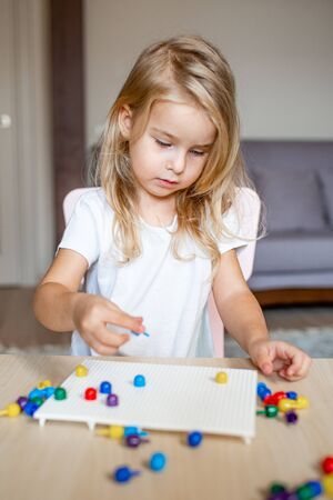 Little blonde girl in a white tshirt playing with plastic multicolor mosaic at home or preschool. Early education concept 写真素材 - 132180891