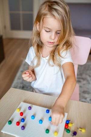 Little blonde girl in a white tshirt playing with plastic multicolor mosaic at home or preschool. Early education concept 写真素材 - 132180899