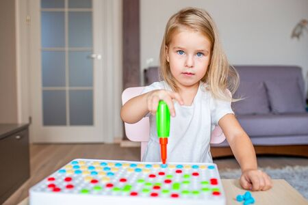Happy pretty little blonde girl sitting at a table at home playing with a toy screwdriver and multicolor screws. Early education concept. Girl looking at the camera. Banque d'images