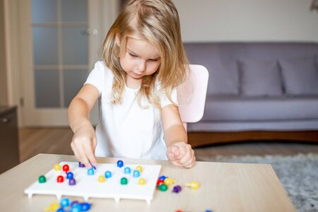 Little blonde girl in a white tshirt playing with plastic multicolor mosaic at home or preschool. Early education concept 写真素材 - 132180927