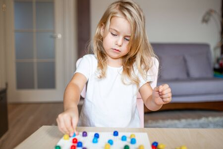 Little blonde girl in a white tshirt playing with plastic multicolor mosaic at home or preschool. Early education concept