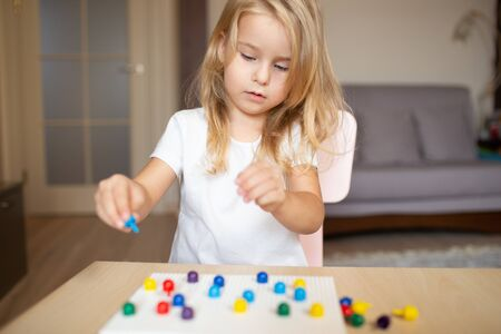 Little blonde girl in a white tshirt playing with plastic multicolor mosaic at home or preschool. Early education concept 写真素材 - 132180932