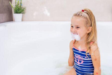 Little blonde girl taking bubble bath in beautiful bathroom.Kids hygiene. Shampoo, hair treatment and soap for children. Kid bathing in large tub. Girl making a beard of a foam