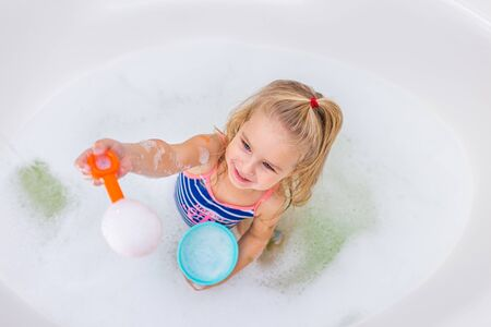 Funny little blonde girl taking bubble bath in beautiful bathroom.Kids hygiene. Shampoo, hair treatment and soap for children. Kid bathing in large tub