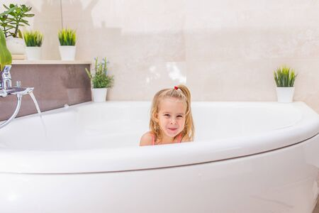 Funny little blonde girl with a sly face taking bubble bath in beautiful bathroom.Kids hygiene. Shampoo, hair treatment and soap for children. Kid bathing in large tub looking at the camera