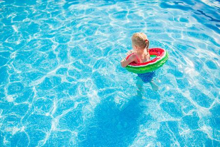 Child with watermelon inflatable ring in swimming pool. Little girl learning to swim in outdoor pool of tropical resort. Water toys and floats for kids. Healthy sport for children