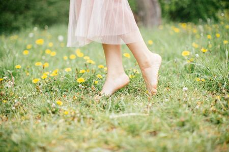 legs of young barefoot women wearing pink dress standing on one leg on green grass with yellow flowers, close up, summer outdoors.