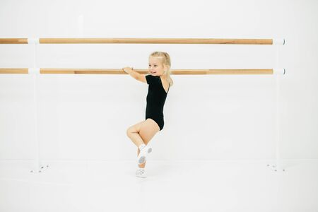 Little ballerina girl in black. Adorable child dancing classical ballet in a white studio. Children dance. Kids performing. Young gifted dancer in a class. Preschool kid taking art lessons. Фото со стока