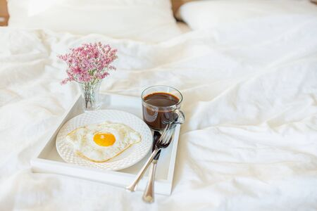 White tray with breakfast on a bed in a hotel room. Fried egg, cup of coffee and flowers in white sheets in light bedroom