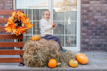 Adorable blonde baby toddler in white knittes jacket sitting on the haystack with pumpkins at porch, playing with apple and laughing. Halloween Thanksgiving card. Imagens