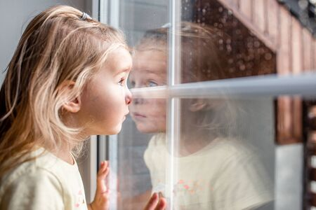 Little adorable blonde toddler girl looking through a window with rain drops on it. Close up portrait