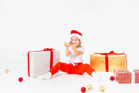Little blonde kids in Santas hat sitting between gift boxes and playing with christmas balls. Isolated on white background. Holidays, new year, x-mas concept. Copyspace.