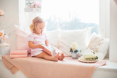 Cute little curly blonde girl in a pink dress with a book on a windowsill