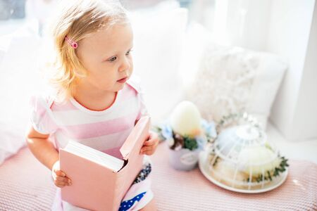 Cute little curly blonde girl in a pink dress with a pink book on a windowsill