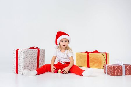 Little blonde kids in Santas hat sitting between gift boxes and playing with christmas balls. Isolated on white background. Holidays, new year, x-mas concept.