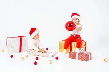 Funny little kids in Santa hat sitting on gift boxes. Isolated on white background. 写真素材