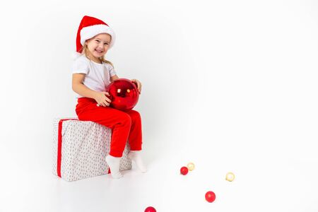 Little smiling girl in santa helper hat sitting on a giftbox with red ribbon and holding red christmas ball, white isolated background. Christmas, winter, happiness concept. 写真素材